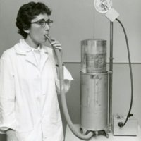 Eleanor Gatz breathing into a device to test the effect of an irritant gas on the lungs