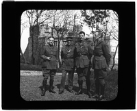 Four men pose in front of brick building