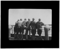 Line of soldiers look out to sea from deck
